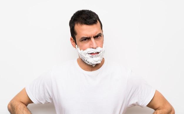 Mężczyzna goli brodę nad odosobnioną biel ścianą gniewną Premium Zdjęcia