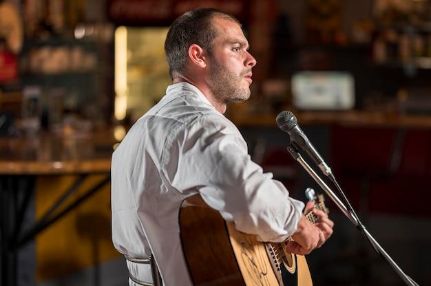 Mężczyzna Gra Na Gitarze I śpiewa Na Mikrofonie W Barze Darmowe Zdjęcia