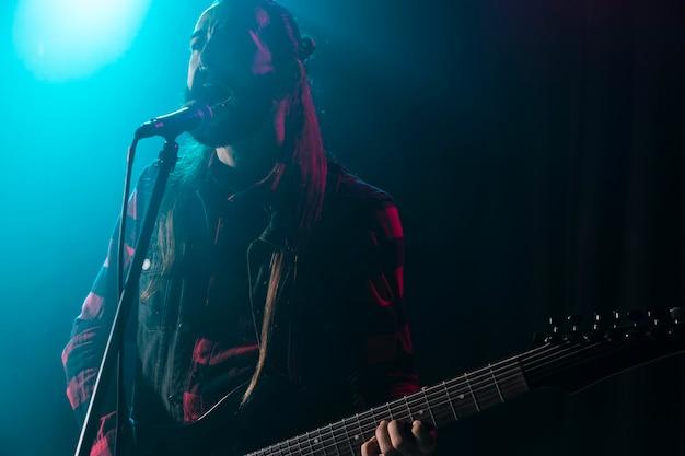 Mężczyzna Gra Na Gitarze I Trzyma Mikrofon Premium Zdjęcia