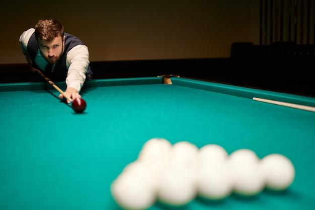 Mężczyzna Gra W Snookera, Chce Strzelić Do Snookera. Przystojny Facet Trzyma Ręce Na Stole Do Snookera. Bilard Premium Zdjęcia