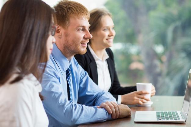 Mężczyzna i dwie kobiety patrząc na laptopa Darmowe Zdjęcia