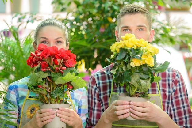 Mężczyzna I Dziewczyna Trzymają Kwiaty Przy Twarzy I Obwąchują Je. Premium Zdjęcia