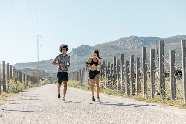 Mężczyzna i kobieta biegnąca wzdłuż drogi Darmowe Zdjęcia