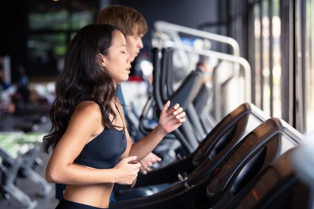 Mężczyzna i kobieta działa na maszynie wypracować zdrowe w siłowni Premium Zdjęcia