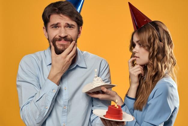 Mężczyzna I Kobieta Na Urodziny Z Babeczką I świecą W świątecznej Czapce Bawią Się I Wspólnie świętują Wakacje Premium Zdjęcia