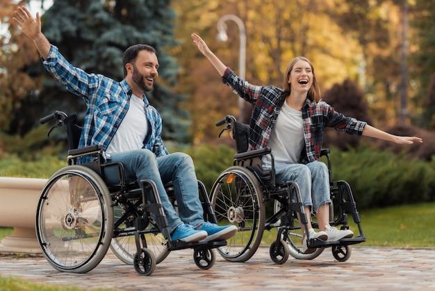 Mężczyzna i kobieta na wózkach inwalidzkich jeżdżą po parku. Premium Zdjęcia