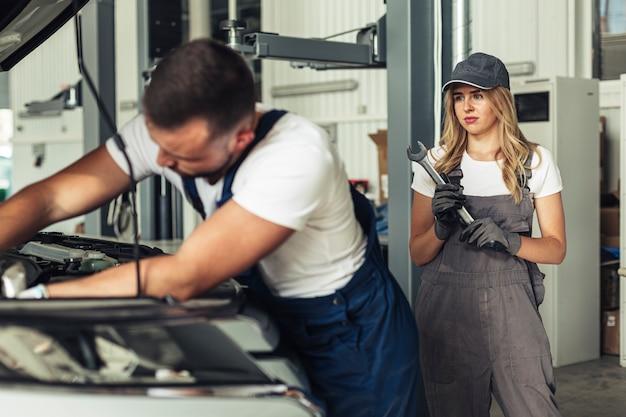 Mężczyzna i kobieta, naprawiając samochód razem Darmowe Zdjęcia
