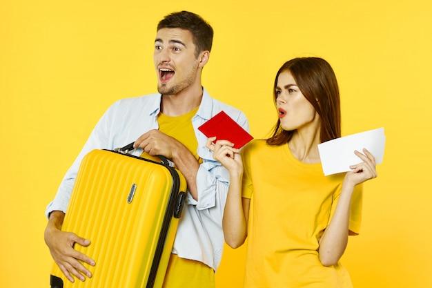 Mężczyzna I Kobieta Podróżnik Z Walizką, Kolorowe Tło, Radość, Paszport Premium Zdjęcia