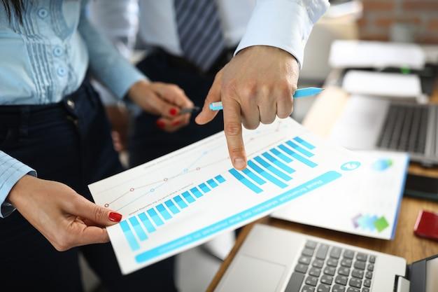 Mężczyzna I Kobieta Ręka Trzyma Wykresy Ze Wskaźnikami Biznesowymi W Biurze. Koncepcja Planowania I Rozwoju Małych I średnich Przedsiębiorstw Premium Zdjęcia