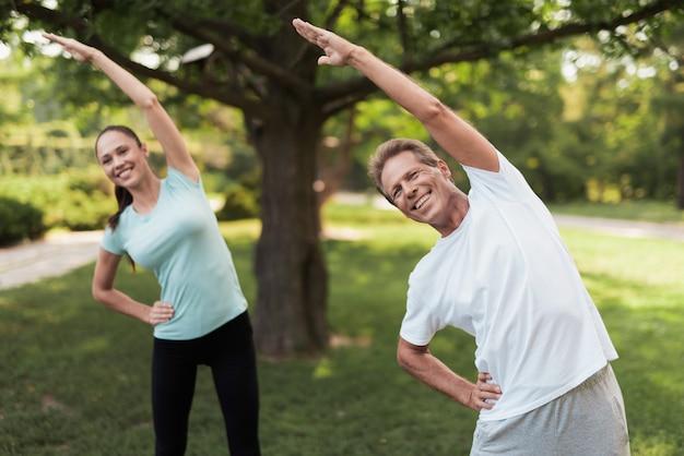 Mężczyzna i kobieta robi ćwiczenia w parku. Premium Zdjęcia