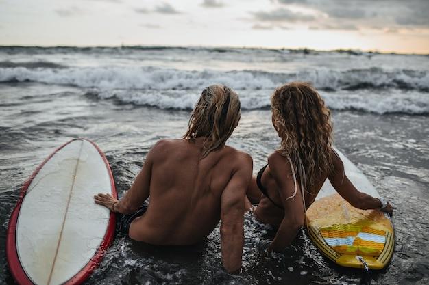Mężczyzna I Kobieta Siedzi Na Plaży Z Deskami Surfingowymi Darmowe Zdjęcia