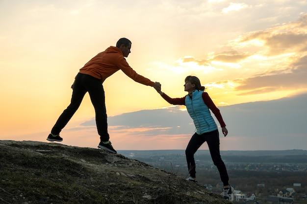 Mężczyzna I Kobieta Turystów Pomagając Sobie Wspinać Kamień O Zachodzie Słońca W Górach. Pary Wspinaczka Na Wysokiej Skale W Wieczór Naturze. Pojęcie Turystyki, Podróży I Zdrowego Stylu życia. Premium Zdjęcia