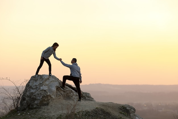 Mężczyzna I Kobieta Turystów Pomagając Sobie Wspinać Kamień O Zachodzie Słońca W Górach Premium Zdjęcia