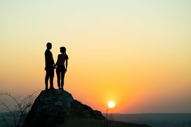 Mężczyzna I Kobieta Turystów Stojących Na Duży Kamień O Zachodzie Słońca W Górach. Dobiera Się Wpólnie Na Wysokiej Skale W Wieczór Naturze. Pojęcie Turystyki, Podróży I Zdrowego Stylu życia. Premium Zdjęcia