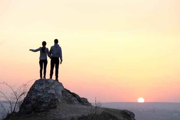 Mężczyzna I Kobieta Turystów Stojących Na Duży Kamień O Zachodzie Słońca W Górach. Para Na Wysokiej Skale W Wieczór Naturze. Pojęcie Turystyki, Podróży I Zdrowego Stylu życia. Premium Zdjęcia
