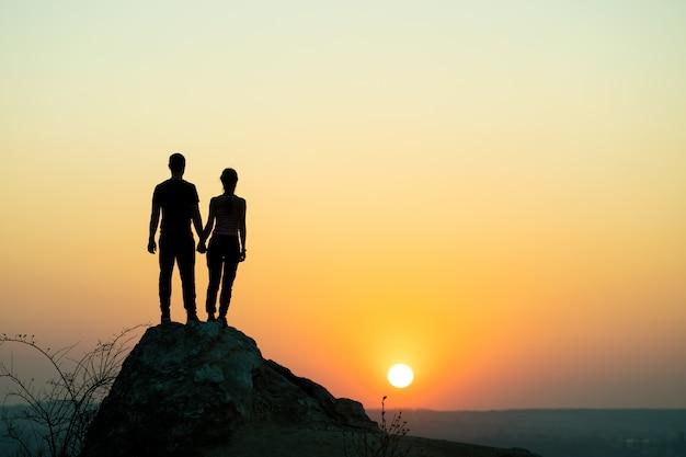 Mężczyzna I Kobieta Turystów Stojących Na Duży Kamień O Zachodzie Słońca W Górach. Premium Zdjęcia