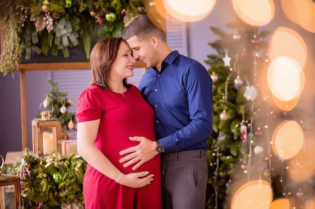 Mężczyzna I Kobieta W Ciąży Obok Choinki Premium Zdjęcia