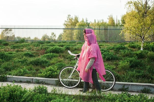 Mężczyzna I Kobieta W Różowych Plastikowych Płaszczach Przeciwdeszczowych Idących Drogą Z Rowerem Na Randkę Darmowe Zdjęcia