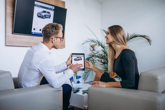 Mężczyzna i kobieta w salonie samochodowym za pomocą tabletu Darmowe Zdjęcia