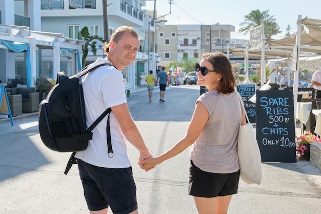 Mężczyzna I Kobieta W średnim Wieku Idą Razem Trzymając Się Za Ręce Premium Zdjęcia