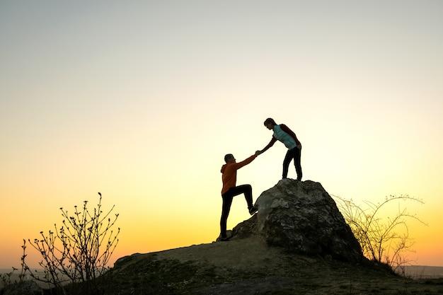 Mężczyzna I Kobieta Wycieczkowicze Pomagają Sobie Wspinać Się Duży Kamień O Zachodzie Słońca W Górach. Pary Wspinaczka Na Wysokiej Skale W Wieczór Naturze. Pojęcie Turystyki, Podróży I Zdrowego Stylu życia. Premium Zdjęcia