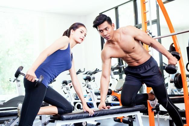 Mężczyzna i kobiety pracujące w siłowni razem Premium Zdjęcia