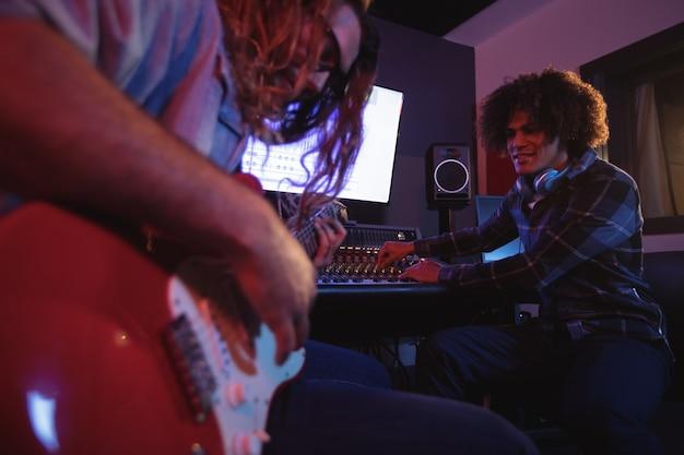Mężczyzna Inżynier Dźwięku Gra Na Gitarze Elektrycznej Darmowe Zdjęcia