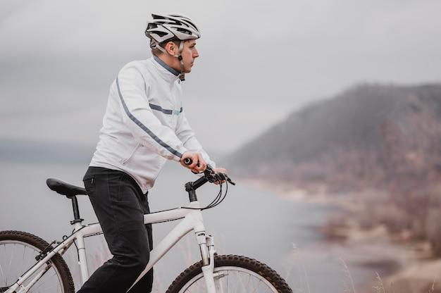 Mężczyzna Jedzie Na Rowerze W Zimny Dzień I Odwraca Wzrok Z Miejsca Na Kopię Darmowe Zdjęcia