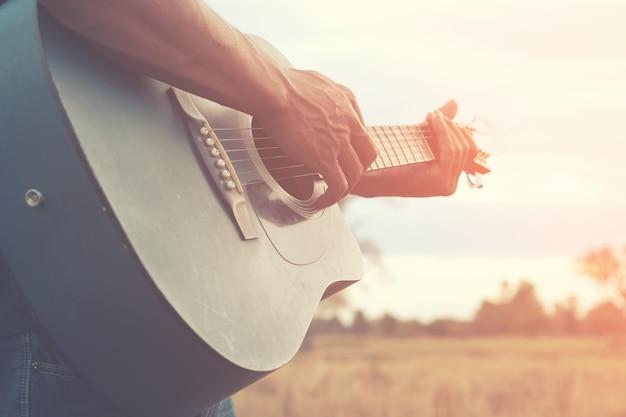 Mężczyzna Jest Gra Na Gitarze W Dziedzinie Trawy W Dzień Relaksu Premium Zdjęcia