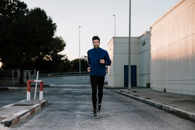 Mężczyzna jogging na ulicy w zmierzchu Darmowe Zdjęcia