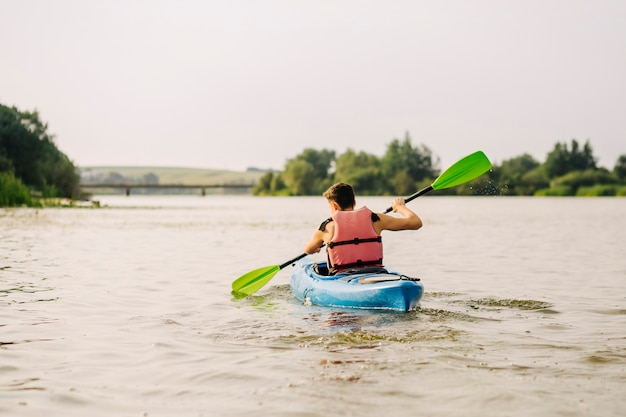 Mężczyzna kayaking na jeziorze z paddle Darmowe Zdjęcia