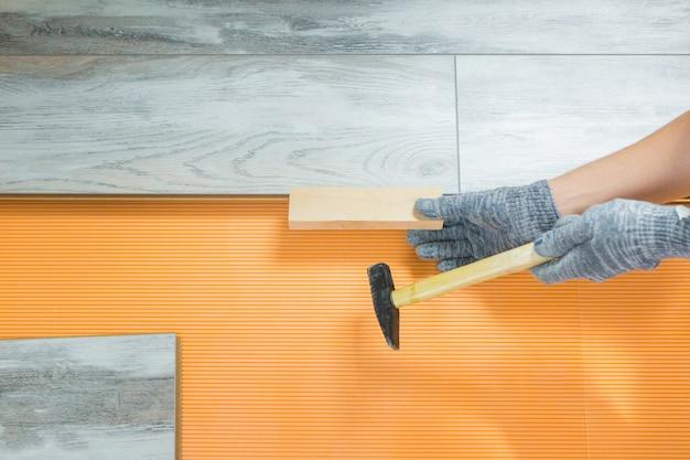 Mężczyzna Kładzie Nową Podłogę Laminowaną. Naprawa W Mieszkaniu. Pracownik Naprawia Podłogę. Proces Układania Laminatu Premium Zdjęcia