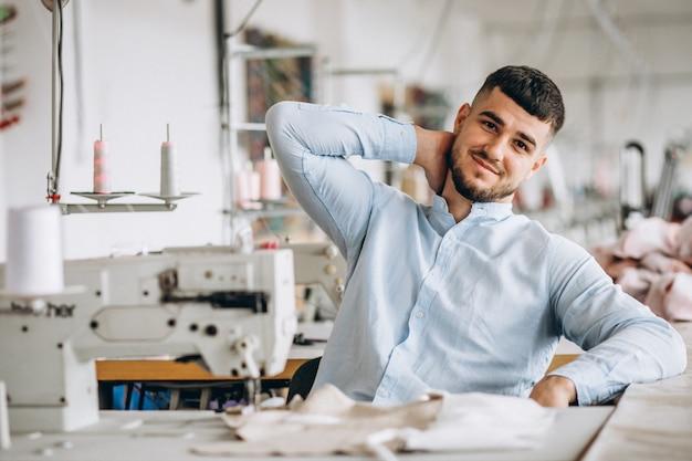 Mężczyzna krawiec pracuje w szwalnej fabryce Darmowe Zdjęcia