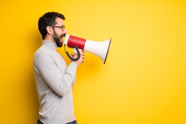 Mężczyzna Krzyczy Przez Megafon Z Brodą I Golfem, Aby Ogłosić Coś W Pozycji Bocznej Premium Zdjęcia