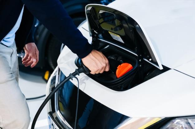 Mężczyzna ładujący samochód elektryczny Premium Zdjęcia