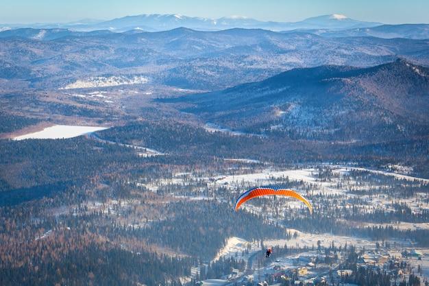 Mężczyzna leci z pomarańczowym spadochronem Premium Zdjęcia