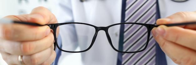 Mężczyzna Lekarz Medycyny Ręce, Dając Parę Czarnych Okularów Premium Zdjęcia