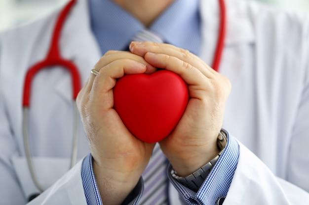 Mężczyzna Lekarz Medycyny Ręce Gospodarstwa I Obejmujące Czerwone Zabawki Serca Premium Zdjęcia