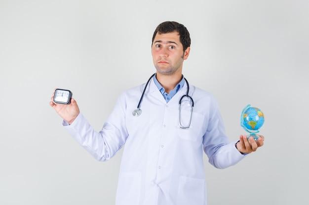 Mężczyzna Lekarz W Białym Fartuchu Trzyma światową Kulę Ziemską I Zegar Darmowe Zdjęcia