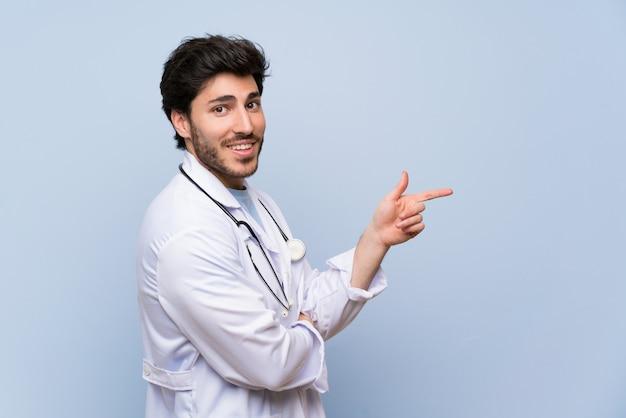 Mężczyzna lekarz wskazując palcem na bok Premium Zdjęcia