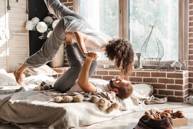 Mężczyzna leżał na łóżku niosąc dziewczynę na nogach Darmowe Zdjęcia