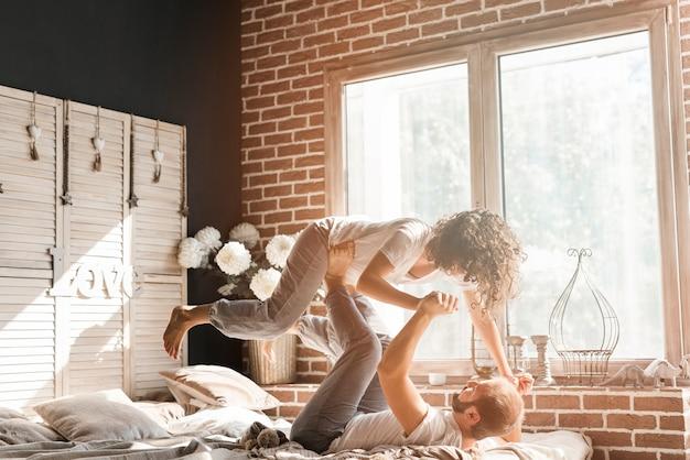 Mężczyzna leżał na łóżku, niosąc żonę na nogach w pobliżu okna Darmowe Zdjęcia