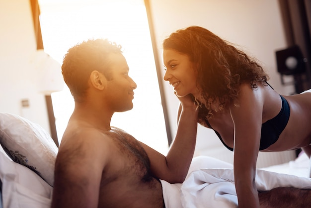 Mężczyzna Leży Na łóżku, A Kobieta Zbliża Się Do Niego Erotycznie. Premium Zdjęcia