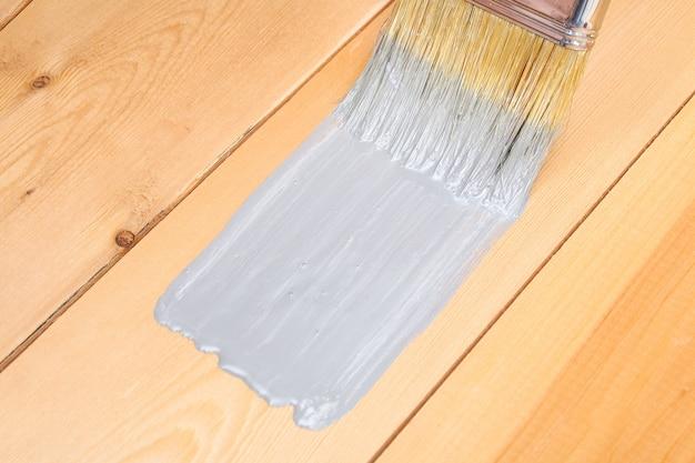Mężczyzna Maluje Drewniane Deski Szarym Pędzlem Premium Zdjęcia