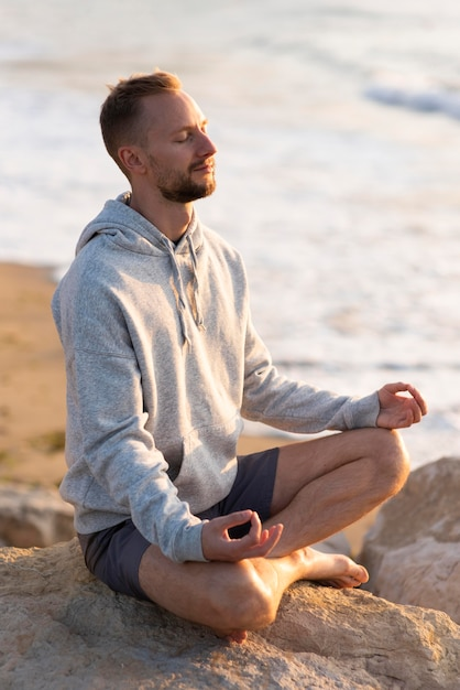 Mężczyzna Medytuje Na Plaży Darmowe Zdjęcia