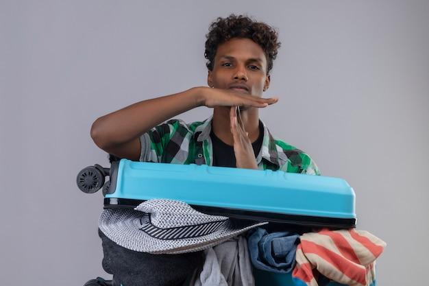 Mężczyzna Młody Podróżnik Afroamerykanin Z Walizką Pełną Ubrań Patrząc Na Kamery, Robiąc Znak Czasu Z Rękami Z Poważnym Wyrazem Twarzy Darmowe Zdjęcia