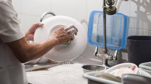 Mężczyzna Mycia Naczyń Na Zlewie W Restauracji Premium Zdjęcia