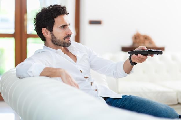 Mężczyzna na kanapie przełącza kanały telewizyjne na pilocie Premium Zdjęcia