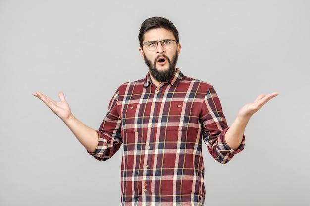 Mężczyzna nad odosobnionym tłem nieświadomy i zmieszany wyrażenie Premium Zdjęcia