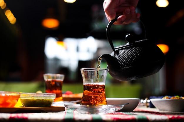 Mężczyzna Nalewanie Herbaty Do Szkła Armudu Z Kamiennego Czajnika Darmowe Zdjęcia